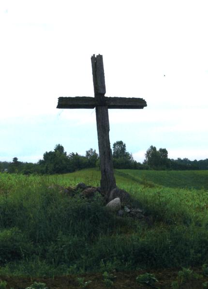 Seniausias kaime kryžius, stovintis tarp Lajų ir Valinčių sodybos. Išlikusi tik kryžiaus viršūnė su metaline Kristaus skulptūrėle. Kryžius stovi atokiau nuo kelio, vidury ariamo lauko, tad vasarą bemaž nematomas. Spėjama, kad jis statytas dar XIX a., greičiausiai čia gyvenusios Šilinskų šeimos rūpesčiu