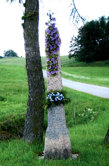 Tašyto raudono granito kryžius stovi kaimo kryžkelėje, netoli Brezgelų sodybos