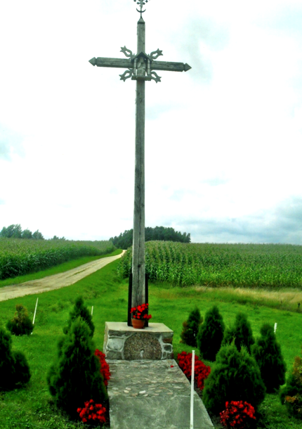 Kryžius prie Grigučių sodybos statytas 2007 m. Ąžuolą šiam tikslui parūpino Antanas Grigutis, o senojo kryžiaus vietoje jį pastatė sūnus Juozas. Kryžius mūsų krašto drožėjo Zenono Knyzos darbo, akmeninį pagrindą su įmūryta girnapuse padarė Jonas Vaznelis iš Punsko