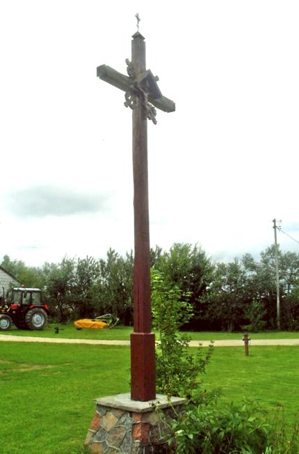 Kryžius prie Gibų sodybos statytas 2002 metais, šios šeimos iniciatyva ir lėšomis. Jį padirbo Zenonas Knyza iš Vidugirių Būdos, akmeninį pagrindą su išražytais Gedimino stulpais padarė Jonas Grigutis iš Vidugirių. Kryžius pastatytas po šeimoje įvykusios tragedijos, tačiau savininkas teigia, jog intencija buvo tiesiog noras pastatyti naują kryžių senojo supuvusio kryžiaus vietoje